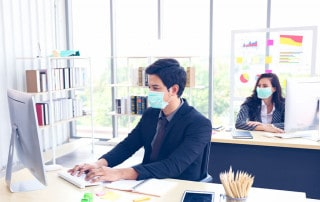 Two office workers working while wearing masks