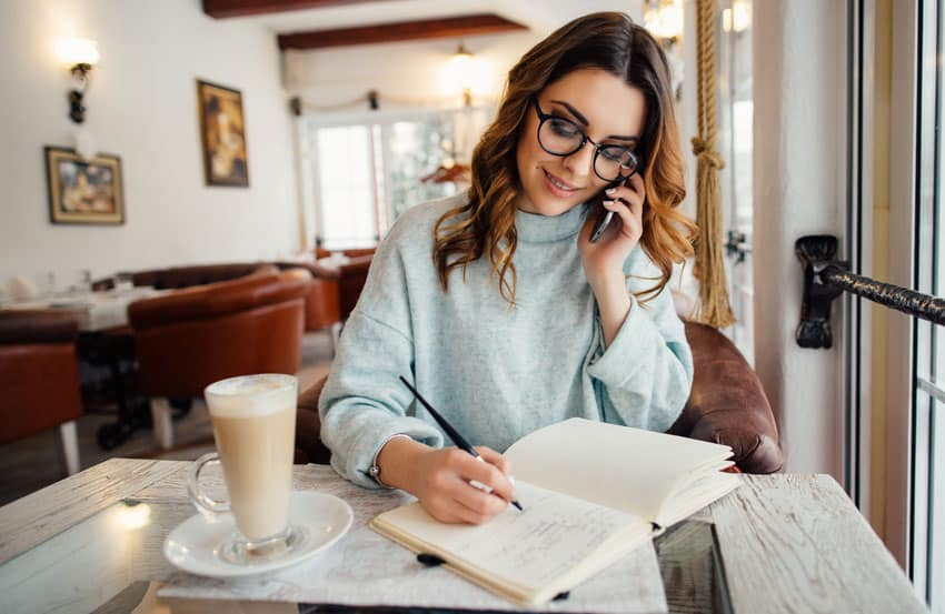 woman working from home taking notes while on a conference call