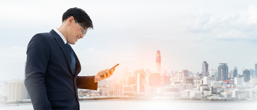 man looking up what is shaping the future of L&D on his cell phone with a view of NYC