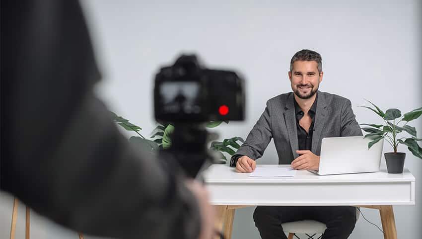 man recording corporate training session on camera