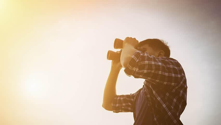 man looking in the horizon with binoculars